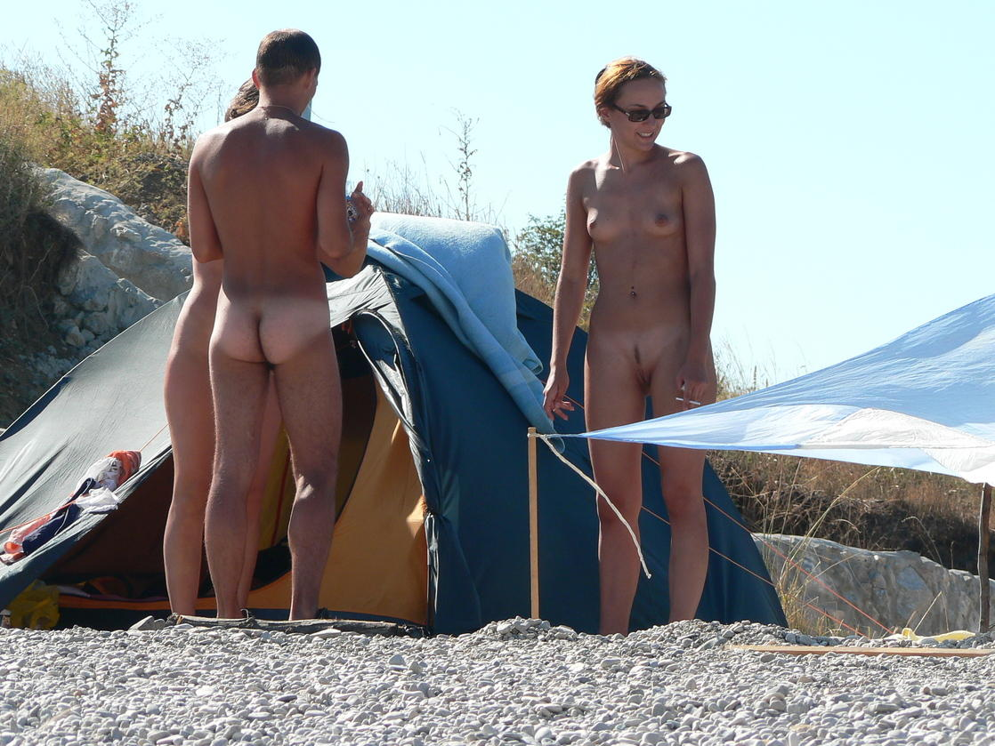 Cold weather caught young nudists naked without clothes on rocky shore