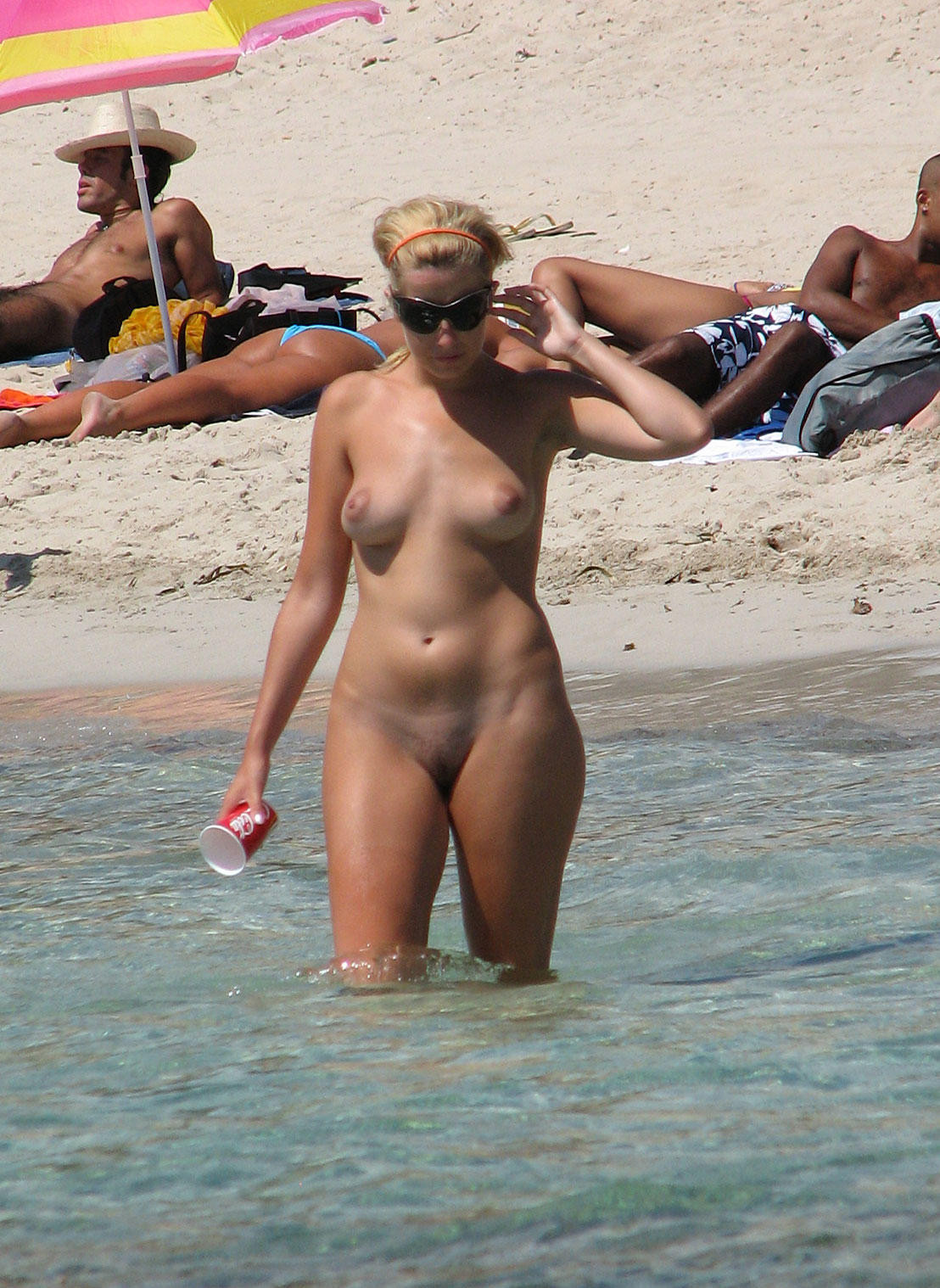 Stunning nude chick takes a quick dip before getting a tan