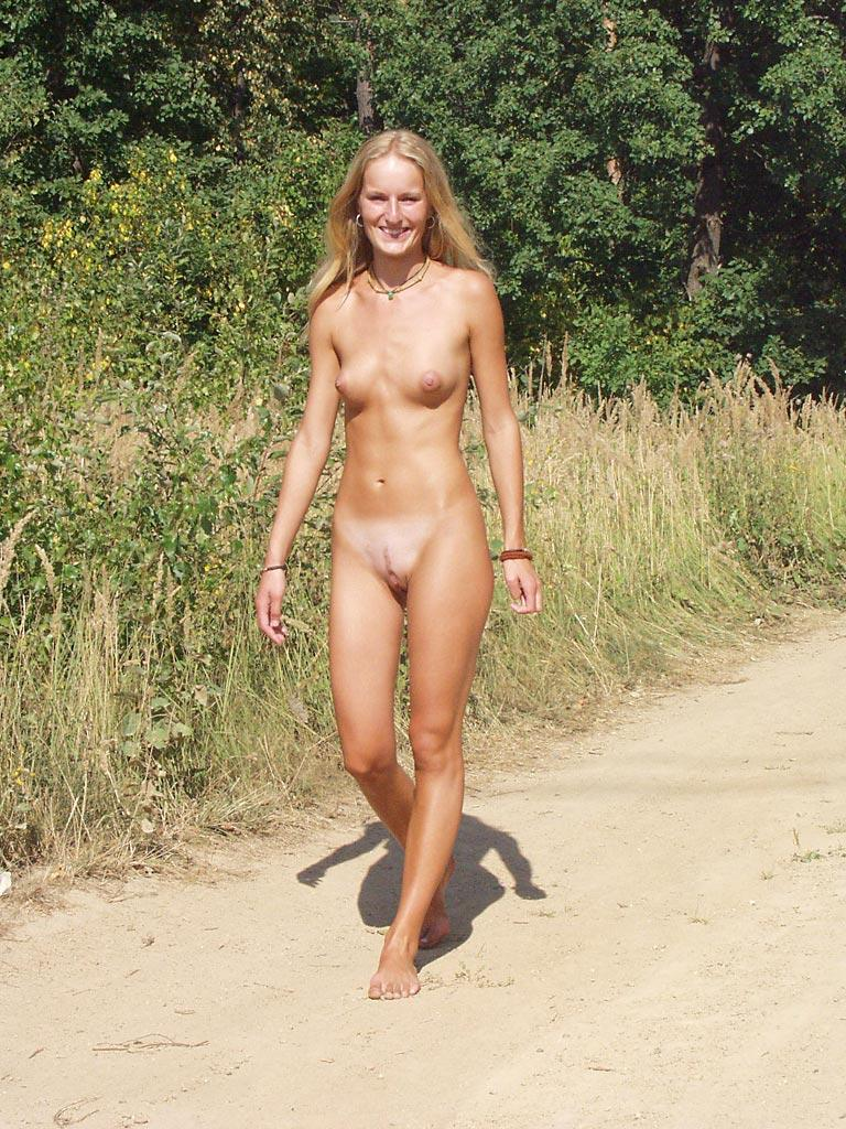 Young nudist chick wears nothing but a smile