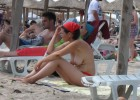 Dark haired chick with a red kerchief sitting topless under the parasol