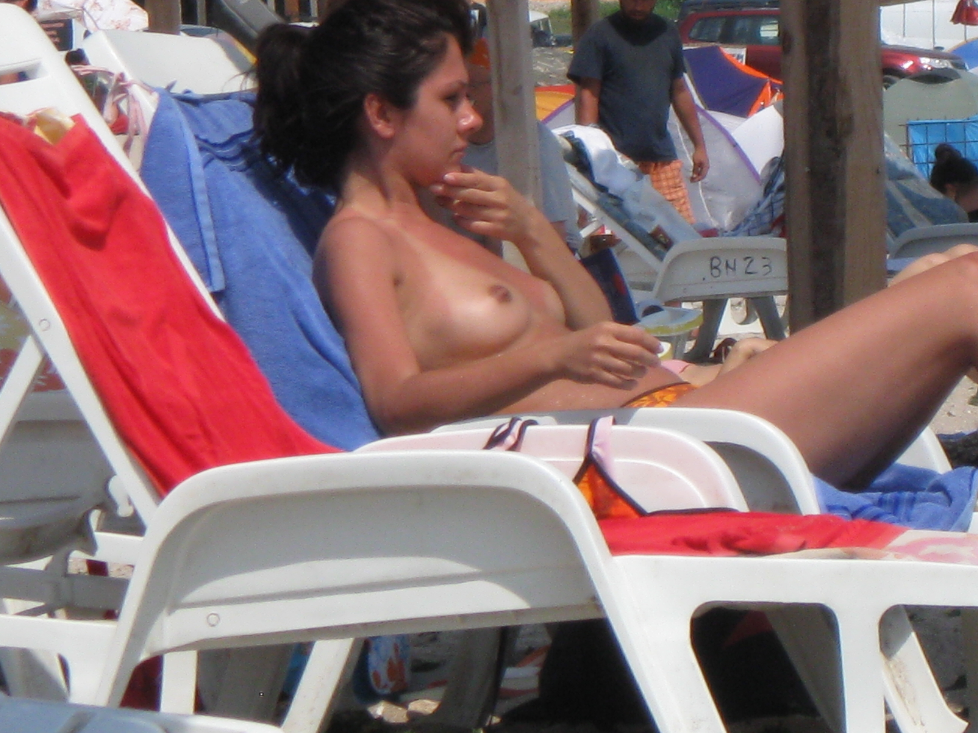 Topless babe wondering if someone is watching her