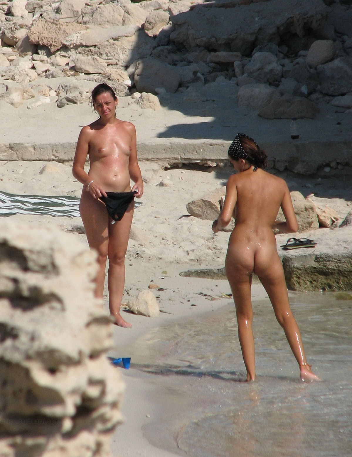 Two nudist girls that are going into the water are voyeurs target