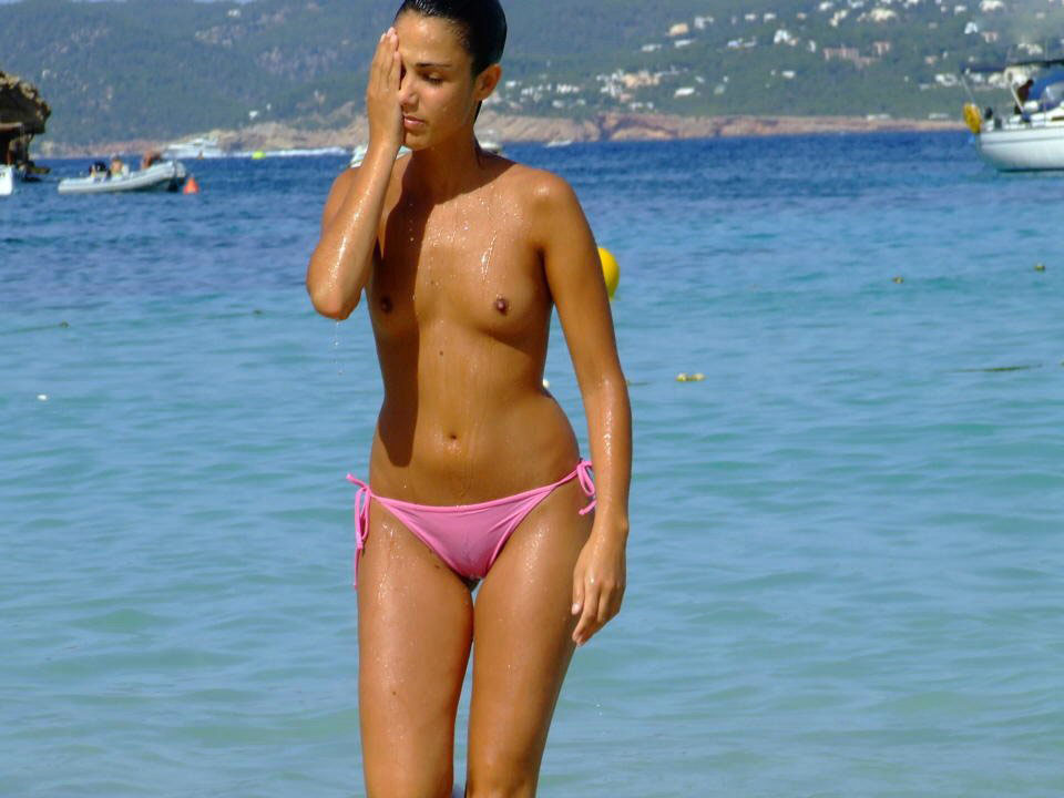 Topless brunette just got out of water